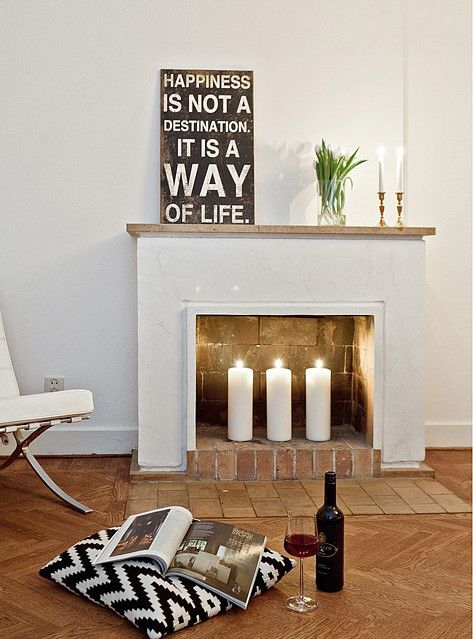 a non-working fireplace with bricks inside and out and pillar candles for styling it right