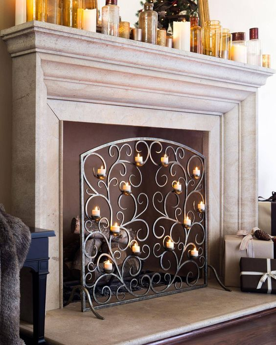 a non-working fireplace with firewood and a refined metal screen with lots of candles brings ultimate elegance