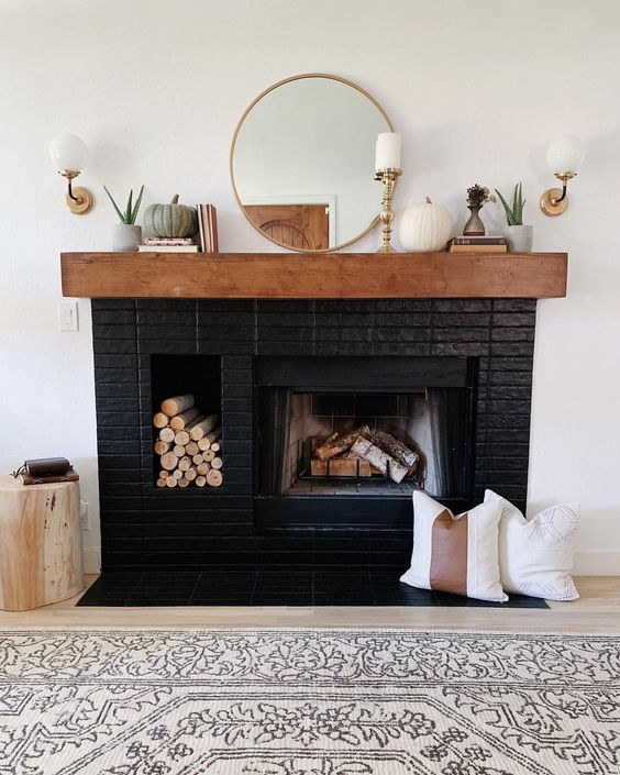 a stylish black brick fireplace with a built-in firewood niche, a stained mantel with elegant decor is a gorgeous idea to try