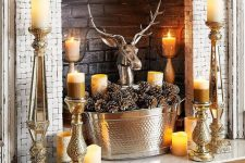 15 a quirky fireplace with bircks, candles all around, a metal bathtub with pinecones and a polished metal deer head