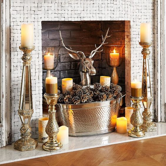 a quirky fireplace with bircks, candles all around, a metal bathtub with pinecones and a polished metal deer head