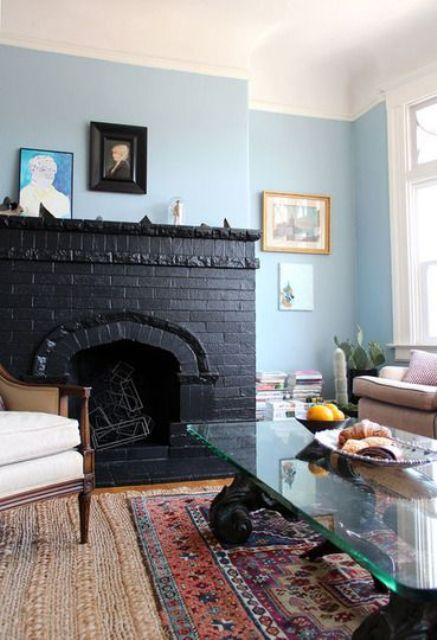 a pastel and neutral living room with a bold statement - a black brick fireplace with geometric figurines inside