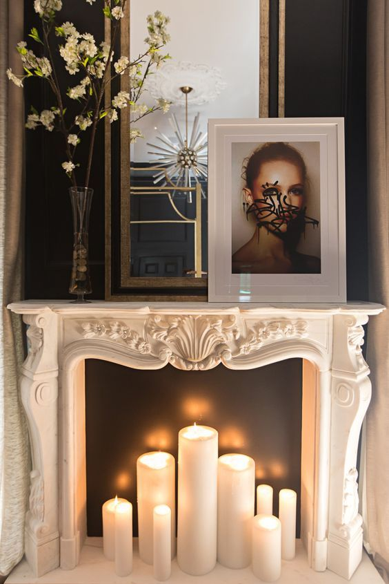 a refined non-working fireplace with a black screen and large pillar candles inside looks sophisticated and chic
