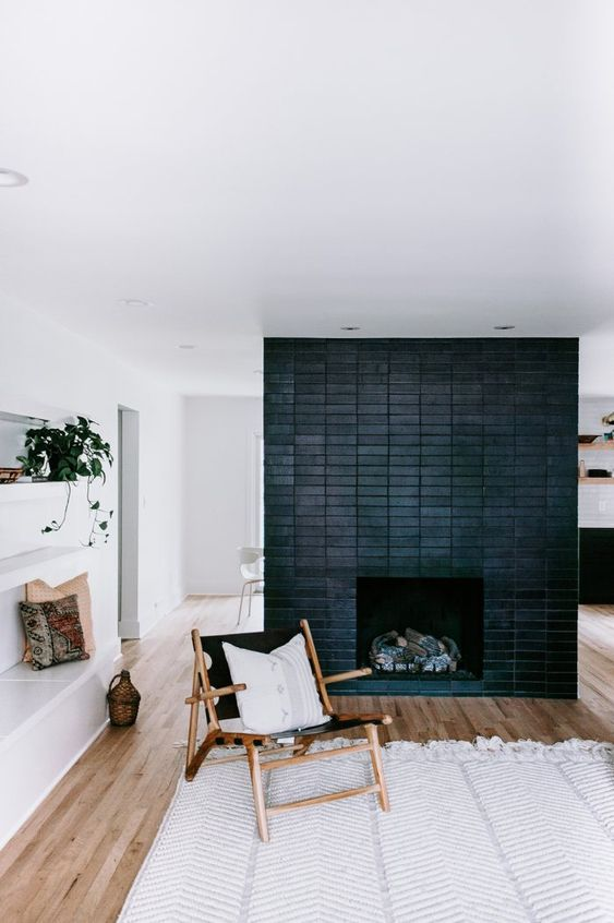 a neutral mid-century boho living room with a black brick fireplace that echoes with the furniture