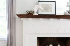 17 a white brick fireplace with pillar candles inside and a stained mantel with decor and plants