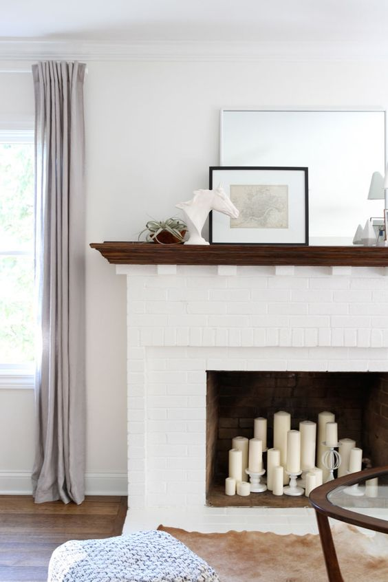 a white brick fireplace with pillar candles inside and a stained mantel with decor and plants