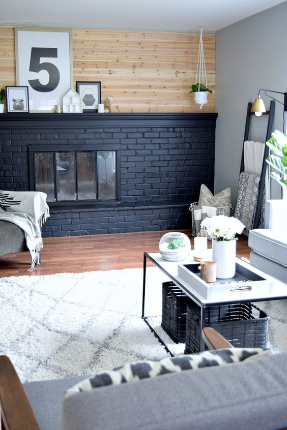 a modern neutral farmhouse living room with a black brick fireplace that contrasts it and a wooden wall over it