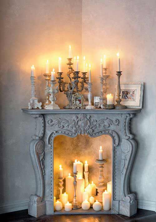 a whitewashed refined fireplace with various candles inside and on the mantel looks gorgeous and creates a mood