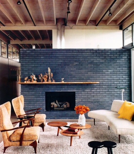 a beautiful navy brick fireplace with a stained mantel and cool decor on it is a decor piece that takes over the whole space