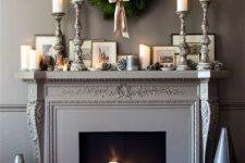 19 an elegant fireplace with a black screen, pillar candles, snowy pinecones and books and the same on the mantel