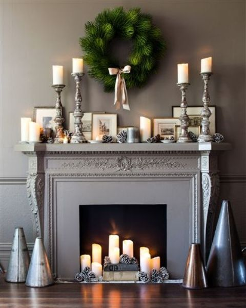 an elegant fireplace with a black screen, pillar candles, snowy pinecones and books and the same on the mantel