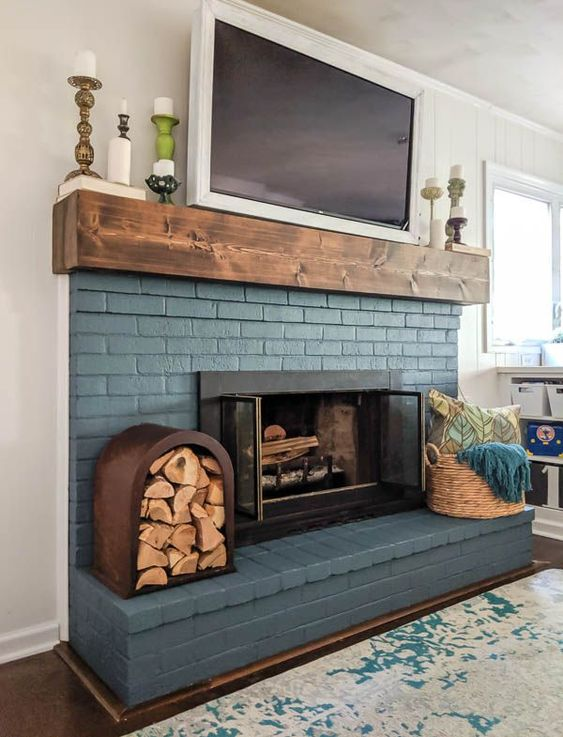 a blue brick fireplace is lovely finished off with a wooden mantel and accented with a basket with towels and a firewood storage