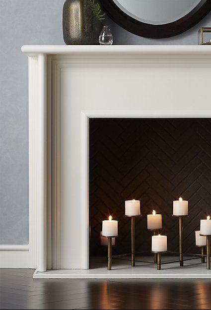 a stylish white fireplace with bricks inside and a chic brass candelabra is a cool alternative to a usual fire