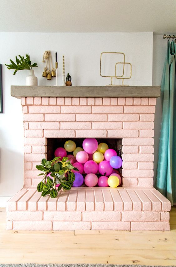 a blush brick fireplace with colorful balloons inside will make a cute girlish accent in your living room