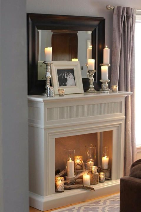 a simple non-working fireplace with candles in various candleholders, tree stumps and wood, some candles on the mantel