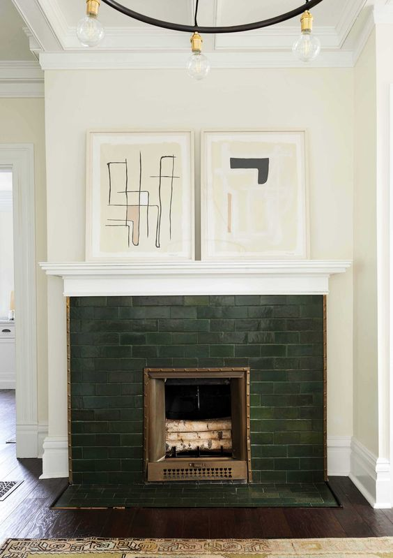a hunter green brick fireplace with copper detailing and abstract artworks on the mantel looks very elegant and refined