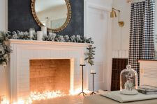 23 a non-working fireplace with lights inside, a snowy greenery garland and candles on the mantel