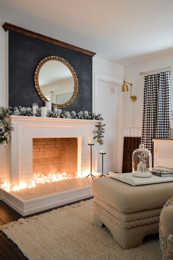 a non working fireplace with lights inside, a snowy greenery garland and candles on the mantel