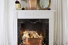 24 a refined non-working fireplace in white and with a black marble part, with a copper bucket with firewood and lights