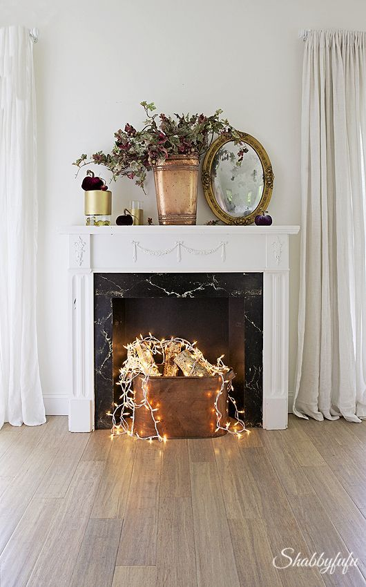 a refined non working fireplace in white and with a black marble part, with a copper bucket with firewood and lights