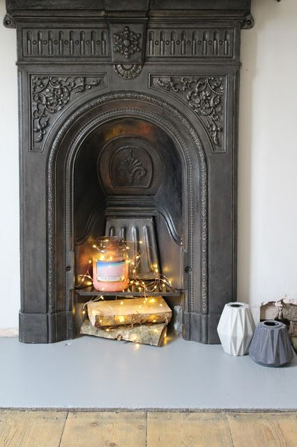 a Victorian fireplace with a large candle, firewood with lights looks modern, fresh and catchy