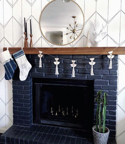 a navy brick fireplace with a wooden mantel and some metallic chess inside is a very fresh take on a traditional piece