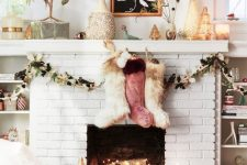 26 a white brick fireplace with firewood with lights, colorful fur stockings and faux leafy garlands for Christmas