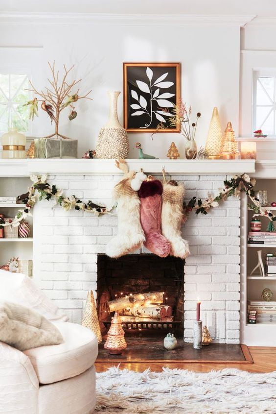 a white brick fireplace with firewood with lights, colorful fur stockings and faux leafy garlands for Christmas