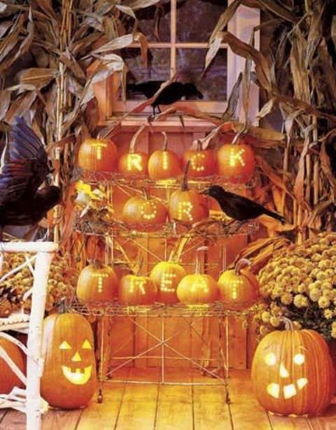 a Halloween arrangement of blackbirds, jack-o-lanterns, hay, husks and blooms is very bright and bold