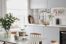 a Nordic kitchen in dove grey, with a white stacked tile backsplash, touches of black and wooden chairs