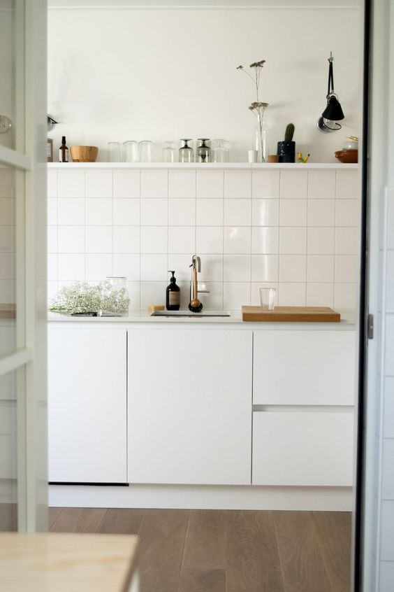 a Scandinavian kitchen in white, with a stacked square tile backsplash and an open shelf over the cabinets