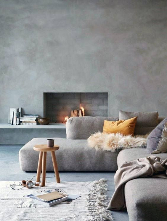a beautiful minimalist living room with chic furniture, a concrete wall and a fireplace and cozy textiles