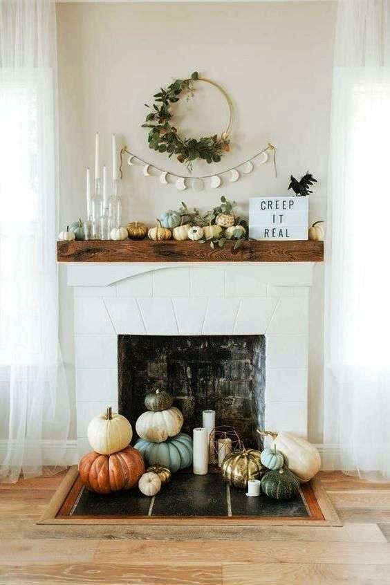 a beautiful natural Halloween mantel with greenery, pumpkins, a blackbird and lots of pumpkins in the fireplace