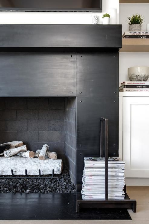 a black metal fireplace boasting a black hearth and a black mantel fixed beneath a television