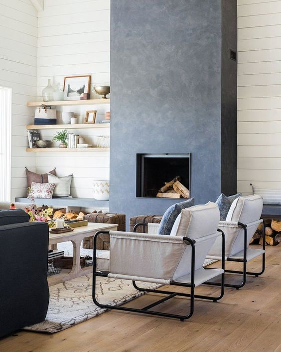 a bold and catchy living room in neutrals, with a grey concrete fireplace and benches with niches for storing firewood