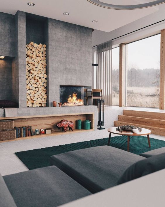a bold and cool modern living room with a large concrete fireplace and a niche for storing firewood is very welcoming