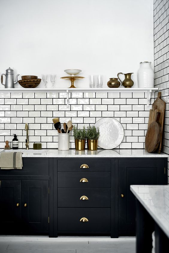 a bold black kitchen with a white subway tile backsplash accented with black grout and touches of gold and brass