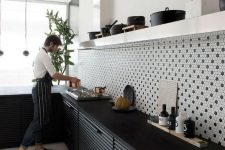 a bold contrasting kitchen with black metal cabinets, white open shelving and black and white penny tile backsplash