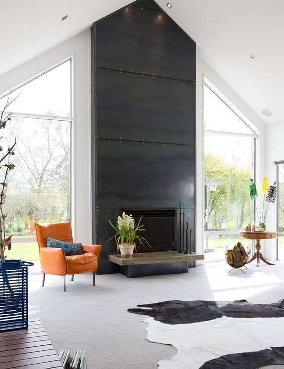 a bold light-filled living room with a fireplace clad with blackened steel sheets and with a bright leather chair in front of it