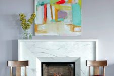 a bold refined nook with a white marble fireplace, fuchsia chairs, a bright artwork and a white leather bench