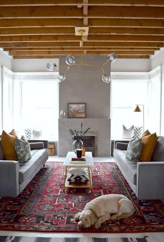 a bright living room done in grey and yellow, with grey sofas and mustard pillows, a concrete fireplace and a yellow chandelier