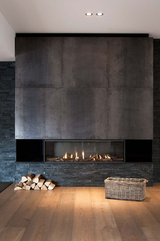 a built-in fireplace with darkened steel sheets over it and faux stone under it feels very woodland-like and cool