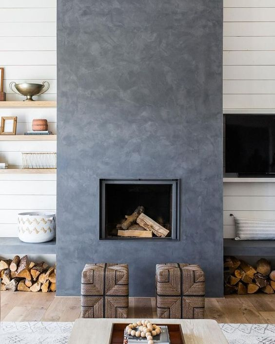 a catchy dark concrete fireplace with woven stools and benches with firewood under them is very cozy