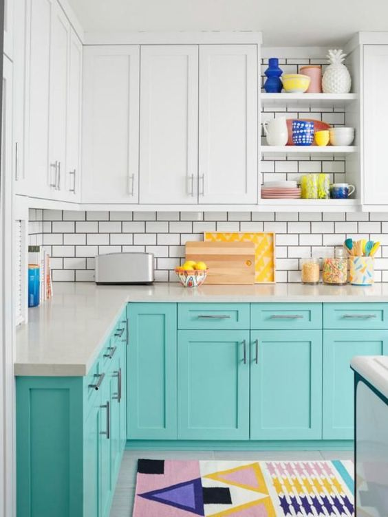 a cheerful turquoise and white kitchen with white subway tiles, colorful accessories and rugs for a fun feel