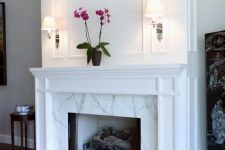 a chic and stylish marble fireplace with some marble on the floor and a vintage white mantel over it is refined
