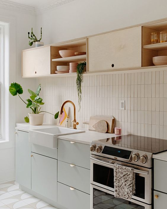 a chic kitchen in dove grey and light-colored plywood, with white countertops and a white stacked tile backsplash
