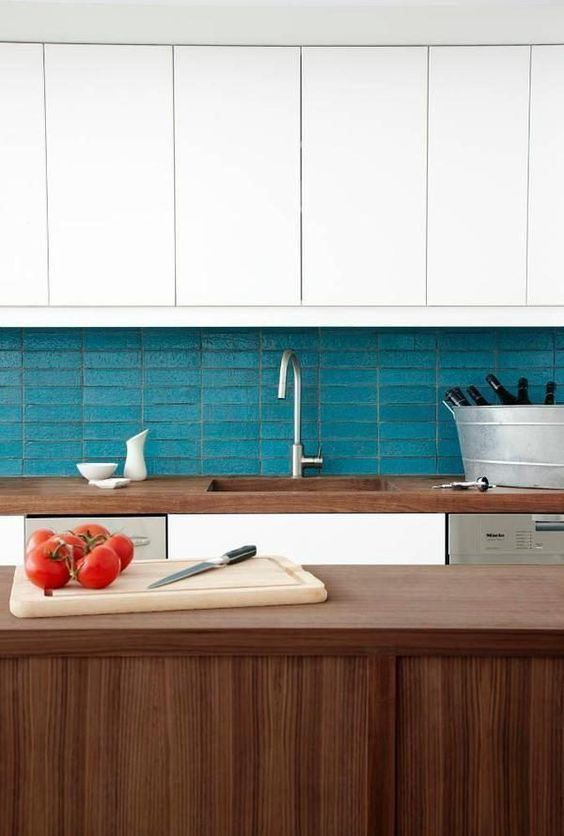 a chic kitchen in white and stained wood, with a blue stacked tile backsplash is very stylish
