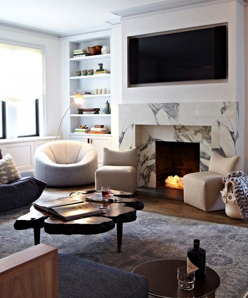 a chic modern living room in neutrals, with a faux fireplace clad with white marble and lit up firewood inside it