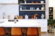a chic modern white kitchen with a navy stacked tile backsplash and borwn leather stools