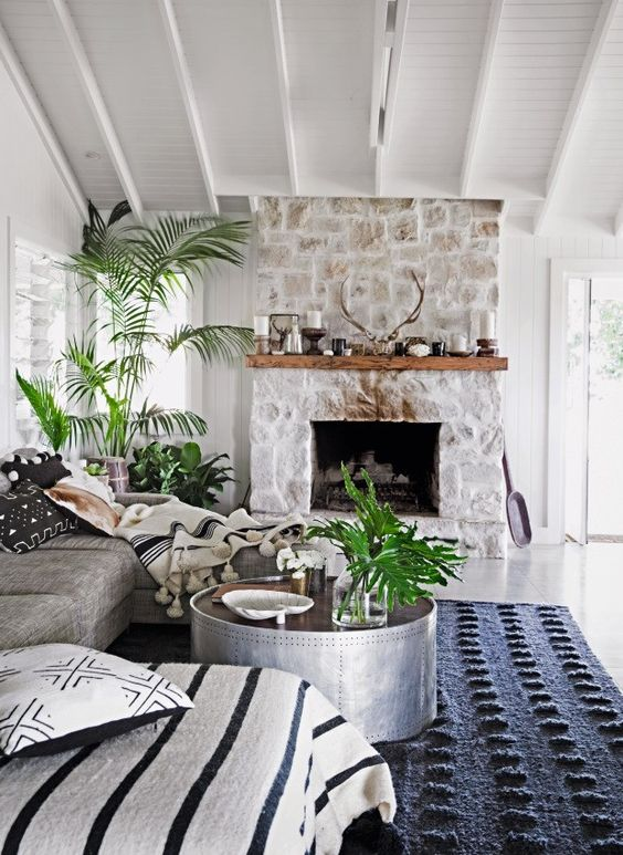a chic monochromatic living room with a whitewashed stone fireplace, a wooden mantel with candles and antlers and potted plants
